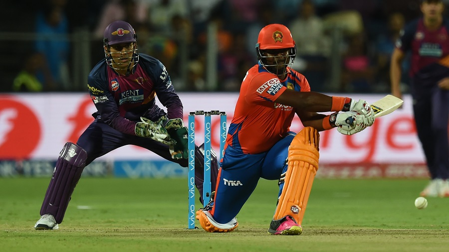 Gujarat Lions Dwayne Smith (R) watched by Rising Pune Supergiants captain Mahendra Singh Dhoni plays a shot during the 2016 Indian Premier League(IPL) Twenty20 cricket match between Rising Pune Supergiants and Gujarat Lions at The Maharashtra Cricket Association Stadium in Pune on April 29, 2016.   / AFP PHOTO / INDRANIL MUKHERJEE