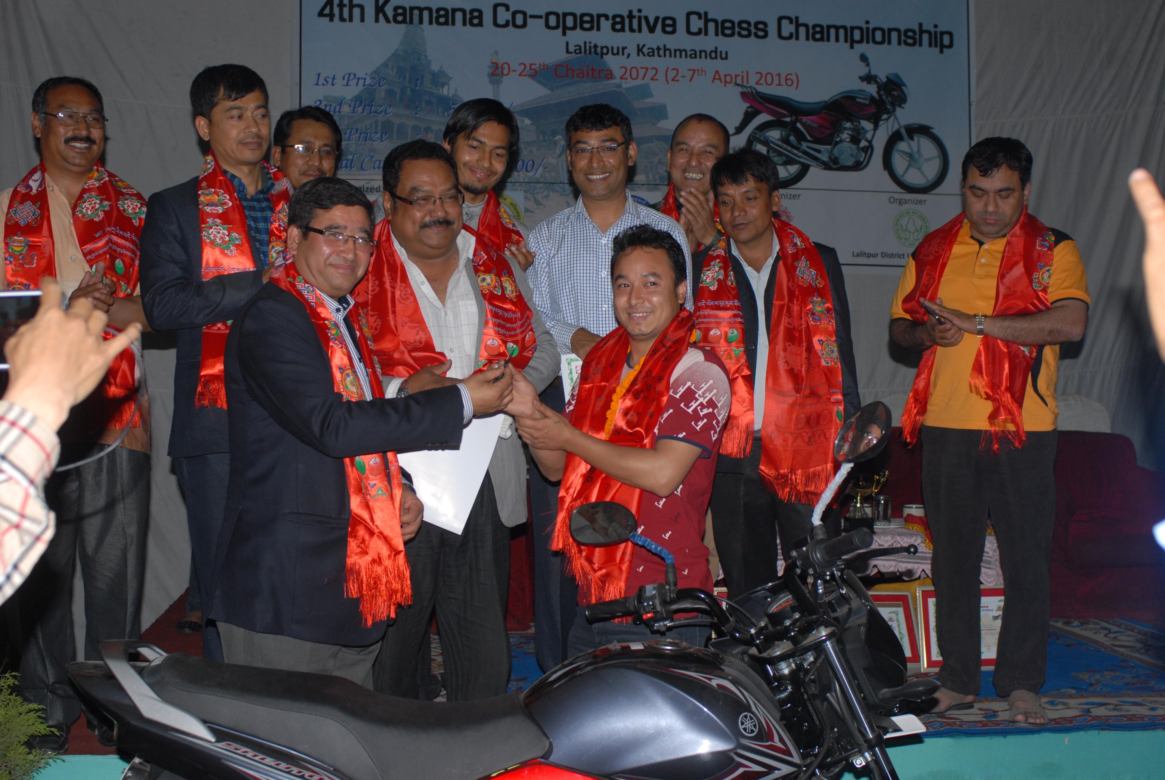 कामना साकोस बुद्धिचालका विजेता सजिन महर्जनलाई मोटरसाइकलको साचो हस्तान्तरण गर्दै नेपाल ओलम्पिक कमिटीका अध्यक्ष जीवनराम श्रेष्ठ ।
