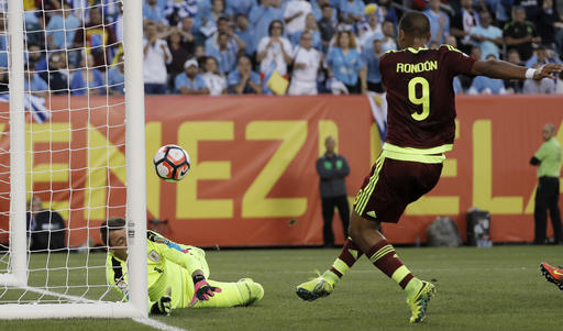 Venezuela's Salomon Rondon, right, scores a goal past Uruguay's Fernando Muslera during the first half of a Copa America Group C soccer match Thursday, June 9, 2016, in Philadelphia. (AP Photo/Matt Slocum)